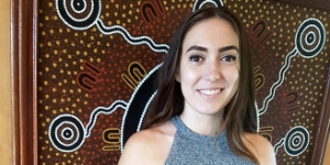 Young Aboriginal woman in front of Aboriginal painting