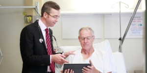 Dr discussing something on an ipad with a patient in bed
